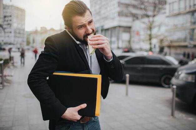 Der vielbeschäftigte mann hat es eilig, er hat keine zeit, er wird unterwegs einen snack essen. arbeiter essen, kaffee trinken, gleichzeitig telefonieren. geschäftsmann, der mehrere aufgaben erledigt.