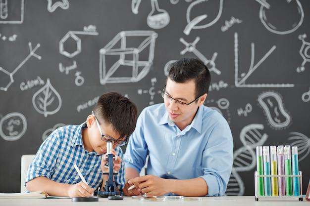 Der vietnamesische chemielehrer erklärt dem schüler das schwierige thema und bittet ihn, auf das mikroskop zu schauen und seine beobachtungen zu schreiben