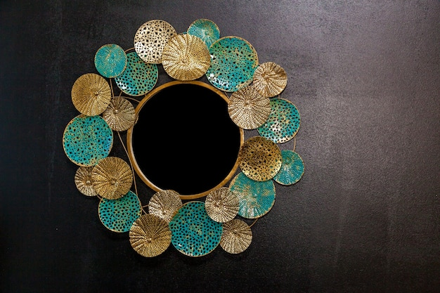 Der vintage spiegel in runder form mit goldenen und türkisfarbenen einsätzen.