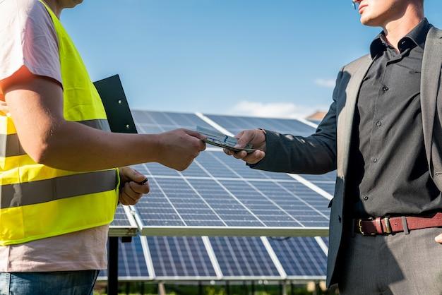 Der vorarbeiter erhält ein dollargehalt von einem geschäftsmann nach der arbeit an der installation von sonnenkollektoren