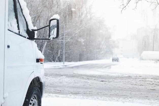 Der vordere teil eines schneebedeckten autos. fahrzeug steht an der schneebedeckten straße bei stürmischem wetter, winter-verkehrssicherheitskonzept