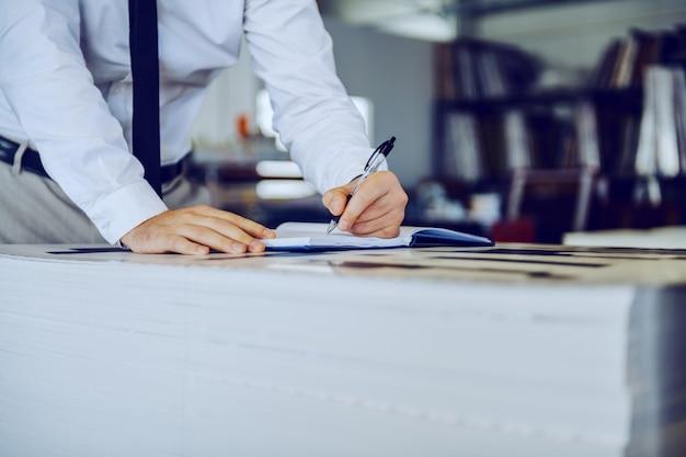 Der vorgesetzte schreibt notizen in das notizbuch, während er in der druckerei steht.