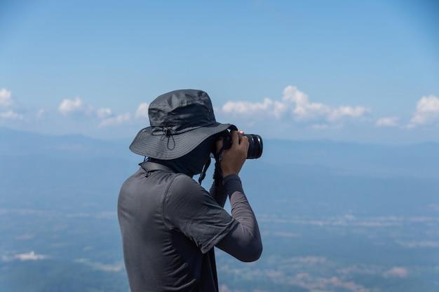 Der wanderer des jungen mannes, der auf bergspitze wandert und foto macht und kamera, thema hält, wird verwischt. ausgewählter fokus