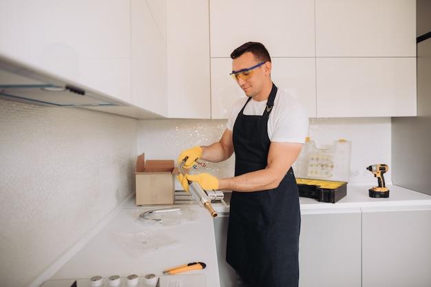 Der wartungsmann wird die sanitäranlagen in der küche installieren