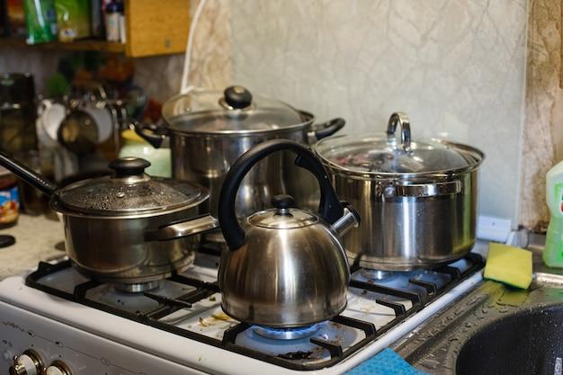 Der wasserkocher und die pfannen stehen auf dem herd. kochen in der küche