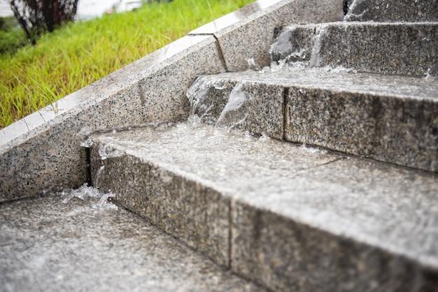 Der wasserstrahl fließt von den stufen der treppe herunter. starkregen. regnerisches herbstwetter.