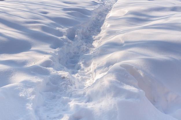 Der weg im weißen schnee. das spiel von licht und schatten.