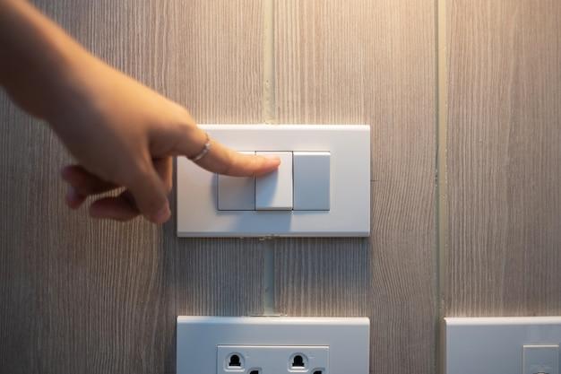 Der weibliche finger wird am lichtschalter an der weißen wand zu hause ein- oder ausgeschaltet. energiespar-, strom-, elektro- und lifestyle-konzepte.