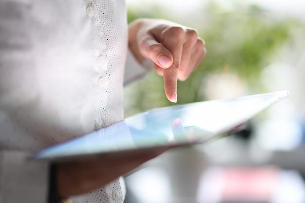 Der weibliche finger zeigt auf den mitgelieferten tablet-bildschirm