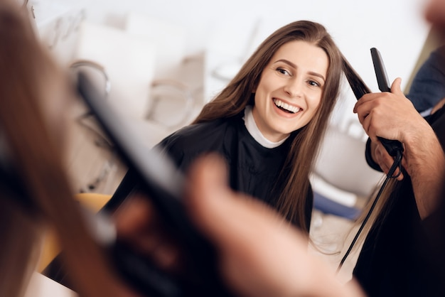 Der weibliche friseur, der haareisen verwendet, richtet haar gerade.