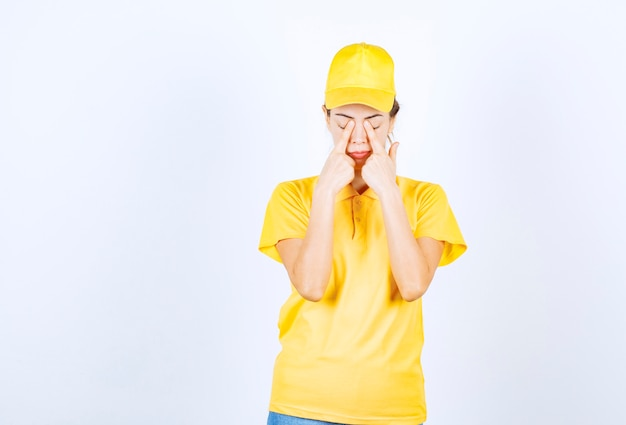 Der weibliche kurier in gelber uniform sieht müde und schläfrig aus.