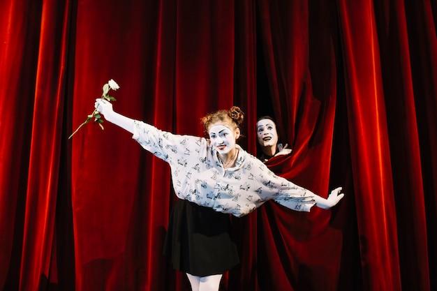 Der weibliche pantomime, der weiß hält, stieg das durchführen auf stadium mit dem männlichen pantomimen, der hinter den vorhang späht