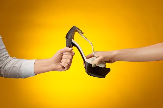 Der weibliche schuh mit weiblicher und männlicher hand auf gelbem papier. shopping- und black-friday-konzept