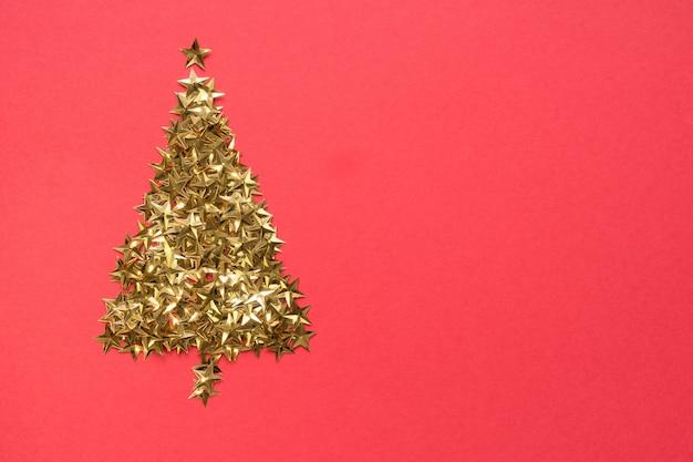 Der weihnachtsbaum, der von den goldenen sternen gemacht wird, funkeln konfettis auf rotem hintergrund. weihnachtsfeiertag.