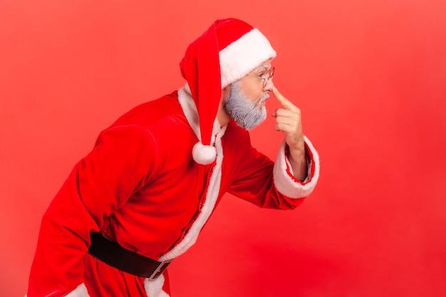 Der weihnachtsmann berührt die nase mit dem finger und tadelt den lügner in der täuschung.