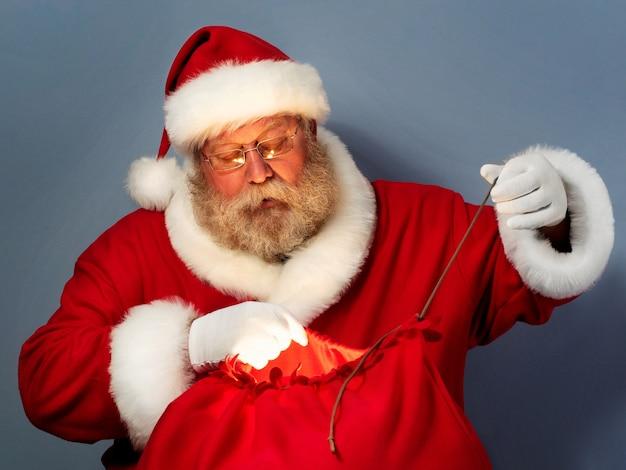 Der weihnachtsmann bindet seine tasche mit geschenken.