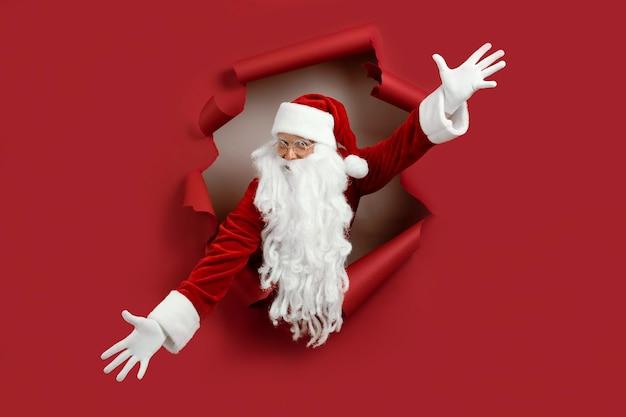 Der weihnachtsmann breitete die arme in verschiedene richtungen aus und schaute emotional durch ein papierloch. bärtiger mann in der weihnachtsmütze, die durch loch auf rotem papier schaut.