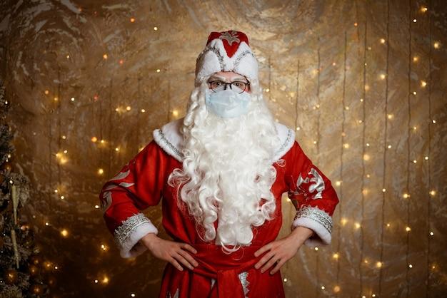 Der weihnachtsmann, der in einer maske auf einem wandhintergrund mit einer girlande posiert, zeigt verschiedene gesten mit seinem ...