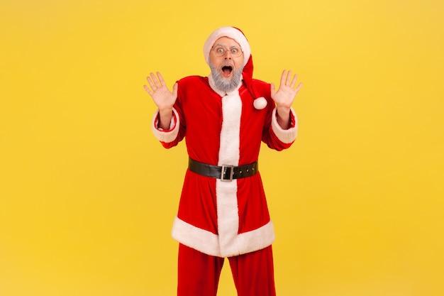 Der weihnachtsmann, der mit großen augen und offenem mund in die kamera schaut, hat aktuelle nachrichten, erhobene arme.