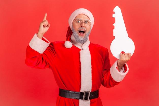 Der weihnachtsmann, der mit offenem mund steht und papierschlüssel hält, hat eine idee für den kauf von immobilien.
