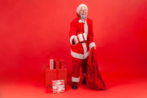 Der weihnachtsmann, der tasche mit geschenken hält und geschenkbox gibt, gratuliert zu den winterferien.