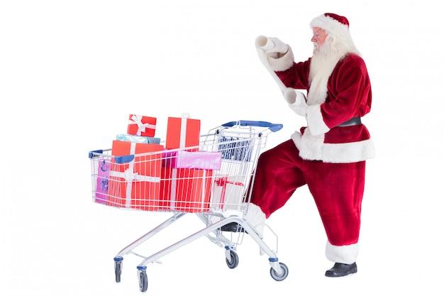 Der weihnachtsmann drückt beim lesen einen einkaufswagen