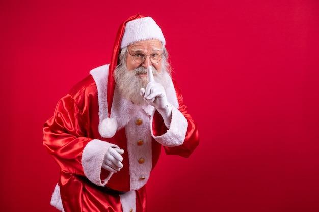 Der weihnachtsmann hält den zeigefinger am mund und schaut in die kamera. schh! geheim halten. stille vertrauliche, ruhige privatsphäre, leises zischen. lustiger nikolaus.