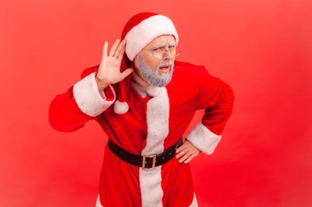 Der weihnachtsmann hält die hand in der nähe des ohrs und hört interessante gespräche und private geheimnisse.