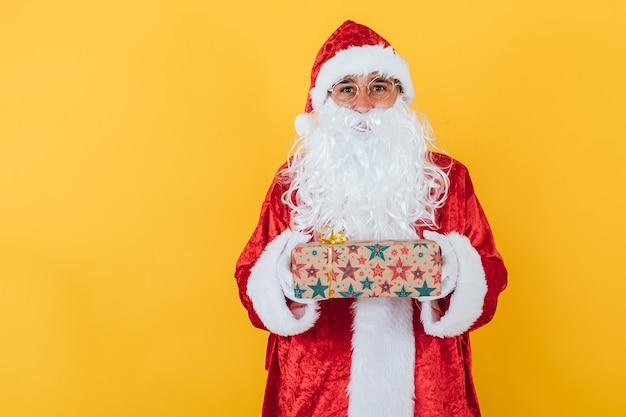 Der weihnachtsmann hält ein geschenk auf gelb
