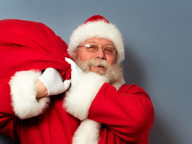Der weihnachtsmann hält eine riesige tüte mit geschenken auf der schulter.