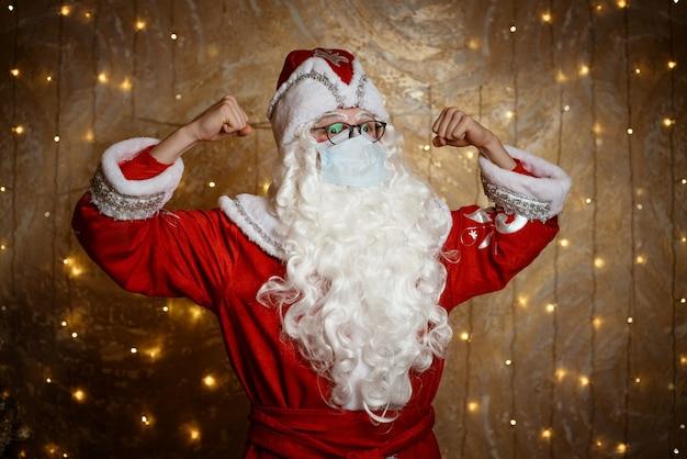 Der weihnachtsmann in brille und maske zeigt gesten mit den händen auf dem hintergrund einer wand mit einem g...