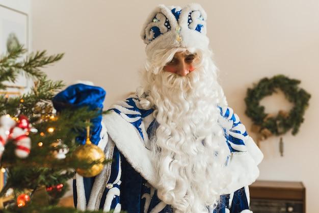 Der weihnachtsmann in einem blauen pelzmantel im weihnachtsinnenraum schmückt einen weihnachtsbaum.