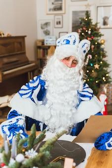 Der weihnachtsmann in einem blauen pelzmantel liest einen brief eines kindes vor dem hintergrund eines weihnachtsbaumes.