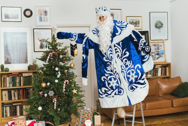 Der weihnachtsmann in einem blauen pelzmantel schmückt einen weihnachtsbaum.