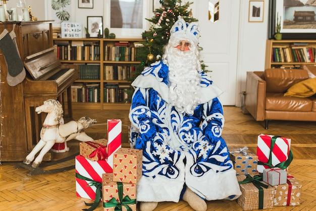 Der weihnachtsmann in einem blauen pelzmantel sitzt im weihnachtsinnenraum vor dem hintergrund