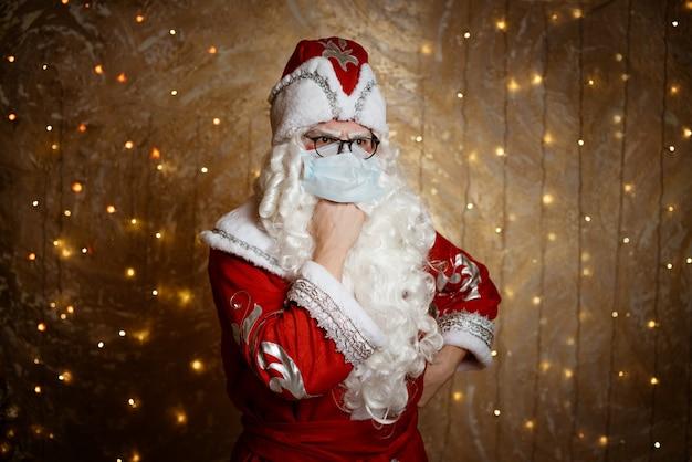 Der weihnachtsmann in gläsern und einer maske gegen ein virus zeigt eine handgeste vor einem wandhintergrund mit ...