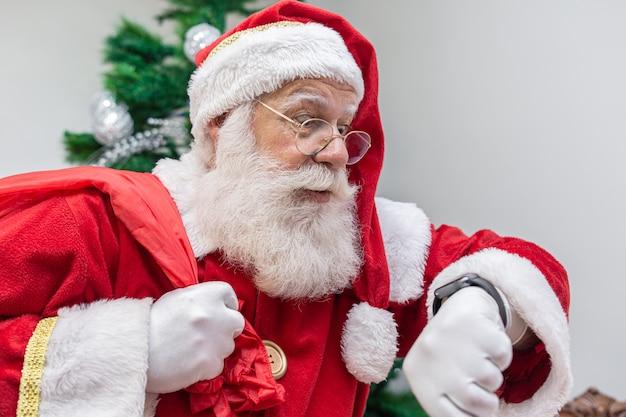 Der weihnachtsmann ist zu spät. er sieht erschrocken auf die uhr. der weihnachtsmann trägt eine moderne uhr. countdown. die zeit kommt.