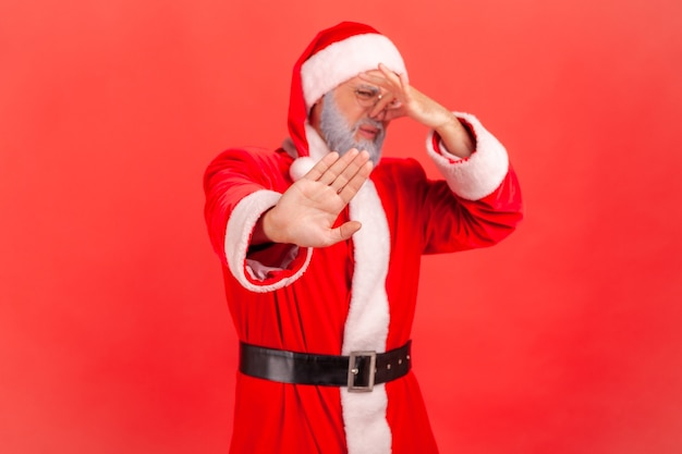 Der weihnachtsmann kneift mit den fingern in die nase, um schlechten geruch zu vermeiden und zeigt stoppgeste