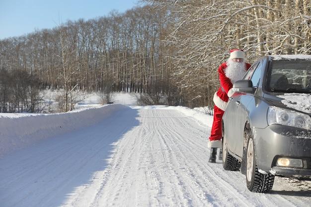 Der weihnachtsmann kommt mit geschenken von außen. der weihnachtsmann im roten anzug mit bart und brille geht den weg zu weihnachten entlang. der weihnachtsmann bringt den kindern geschenke.