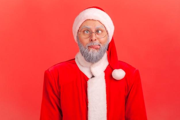 Der weihnachtsmann kreuzt die augen, die zunge raus, sieht verrückt und dumm aus, albert herum, hat spaß.