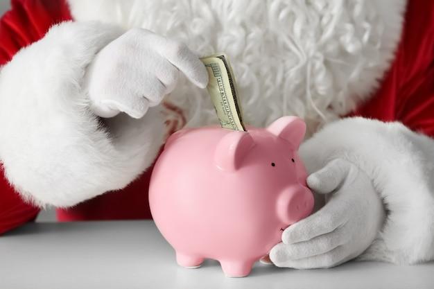 Der weihnachtsmann legt am tisch geld ins sparschwein