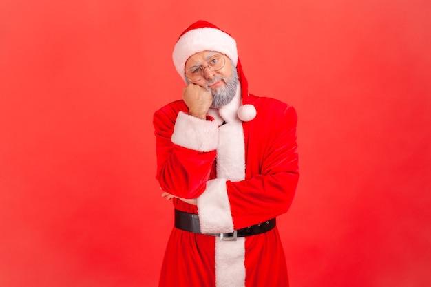 Der weihnachtsmann lehnt sich an die hand und schaut desinteressiert in die kamera, hört einer langweiligen geschichte zu.