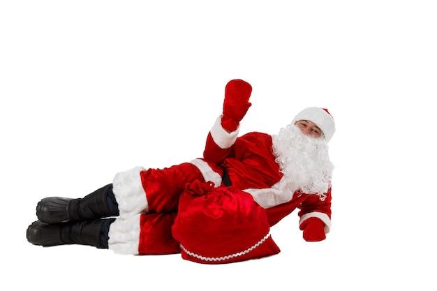 Der weihnachtsmann liegt mit einer tüte geschenke.