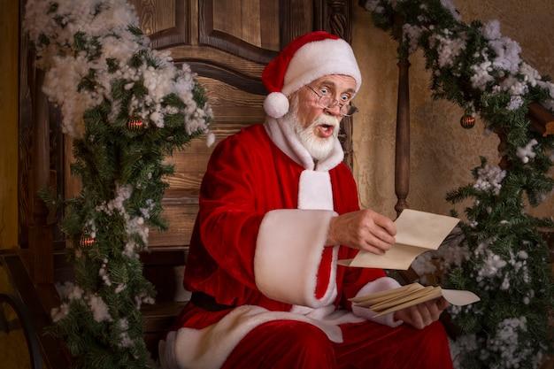 Der weihnachtsmann liest die briefe auf der veranda des geschmückten hauses.