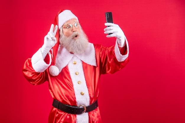 Der weihnachtsmann macht ein selfie mit dem smartphone