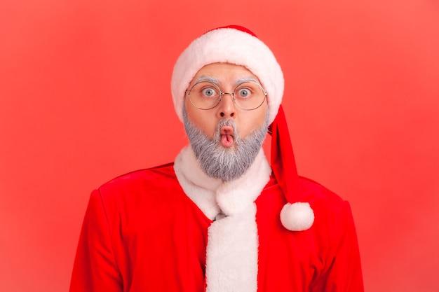 Der weihnachtsmann macht fischgesicht mit schmollmund und überraschten schockierten ausdruck, der mit großen augen schaut.