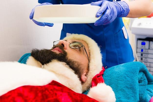 Der weihnachtsmann macht kosmetische eingriffe in der spa-klinik.