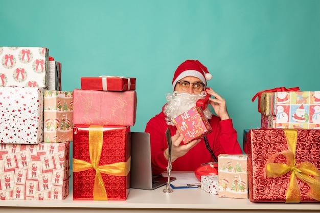 Der weihnachtsmann mit hut arbeitet in seinem büro mit geschenken und bereitet sich auf den urlaub vor.