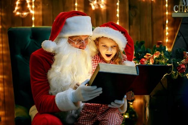 Der weihnachtsmann öffnet und liest ein zauberbuch mit einem kleinen süßen, erstaunten mädchen im pyjama