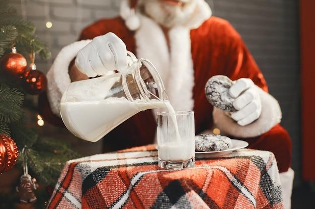 Der weihnachtsmann ruht sich am weihnachtsbaum aus. haus dekoration. geschenk für den weihnachtsmann.